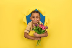 Smiling African American boy with bouquet of tulip flowers peeps out from a torn paper yellow background. Concept of St. Valentine's day, mother's day, eighth of March.