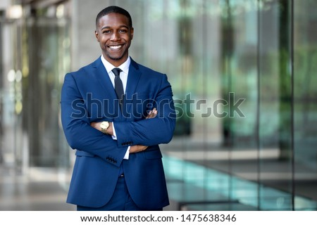 Smiling african american businessman CEO standing proud with arms crossed outside office workplace, colorful, reflective glass building, copy space