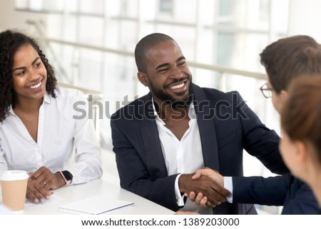 Smiling african American businessman in suit handshake male colleague get acquainted at office meeting, excited black man employee shake hand greeting with business partner a briefing