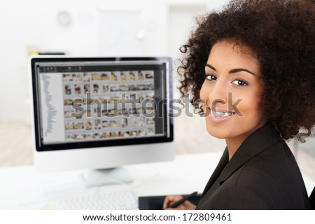 Smiling African American businesswoman editing photographs visible on her computer screen as she turns to smile at the camera