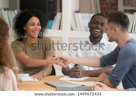 Smiling African American businesswoman handshaking with business partner at meeting, greeting, businessman congratulating mixed race employee with promotion, celebrating successful work results