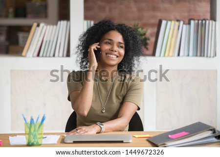 Smiling African American businesswoman talking on phone at work, friendly female manager, advisor consulting client, having pleasant conversation, employee chatting with friend during break