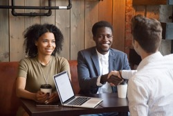 Smiling african american couple shaking hands to mortgage insurance broker, financial advisor or agent at cafe meeting, happy black woman and man handshaking white lawyer or consultant making deal