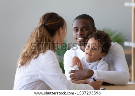 Smiling african American dad and little biracial son visit female young doctor talking about health problems, positive ethnic father with small boy child do checkup examination at woman pediatrician