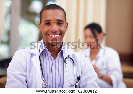 Smiling african-american doctor making with colleagues behind