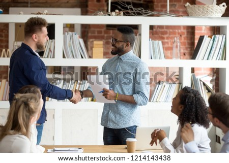 Smiling African American employer handshake millennial worker greeting with good work result during meeting, happy black CEO shake hand of Caucasian employee congratulating with success at briefing #1214143438