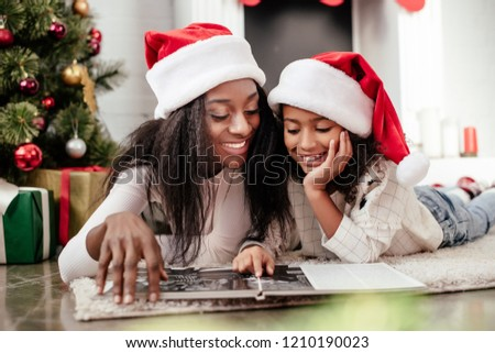 smiling african american family in santa claus hats looking at photo album in decorated room for christmas at home