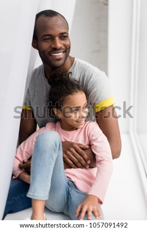 smiling african american father and daughter sitting on windowsill #1057091492