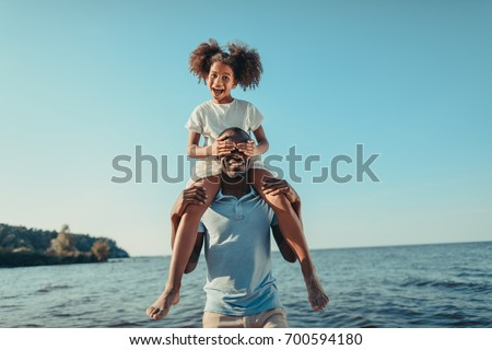 smiling african american father carrying adorable little daughter on beach