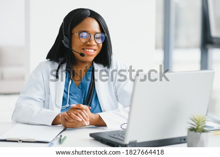 Smiling african american female doctor gp wears white medical coat using laptop computer at workplace gives remote online consultation, working on pc, consulting patient in internet telemedicine chat.