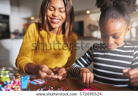 Smiling African American female parent in yellow sweater working with cute child in striped shirt on beading project at table in kitchen