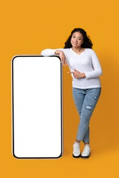Smiling African American Lady Leaning And Pointing At Big Smartphone With Blank White Screen, Showing Copy Space For Your App Or Website Design, Standing Over Yellow Studio Background, Mockup Image