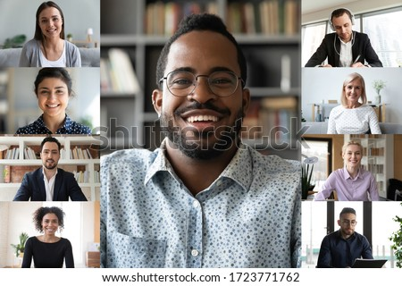Smiling african American male employee talk speak on video call with multiracial work colleagues, diverse businesspeople coworkers have online webcam conference on computer, engaged in web briefing
