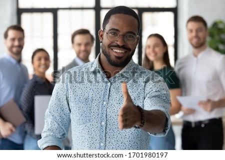 Smiling African American male employer in glasses stretch hand welcome new employee or intern in office, happy biracial boss or businessman meet greet newcomer at workplace, employment concept
