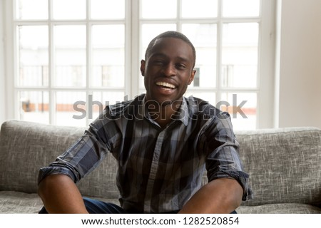 Smiling african american male vlogger life coach looking at camera sitting on couch, positive friendly black millennial single man talking making video call vlog at home, dating online, portrait