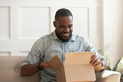 Smiling african american man consumer open cardboard box get postal parcel, happy black male customer receive carton package sit on sofa at home satisfied with fast shipment online purchase delivery