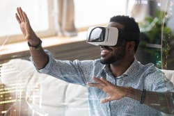 Smiling African American man in VR glasses enjoying augmented reality close up, sitting on couch at home, pointing at virtual reality cityscape, interacting with cyberspace, using electronic device