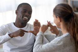 Smiling african American man sit on couch show hand gestures talking with female friend at home, international disabled hearing impaired couple or spouses use sign language communicating
