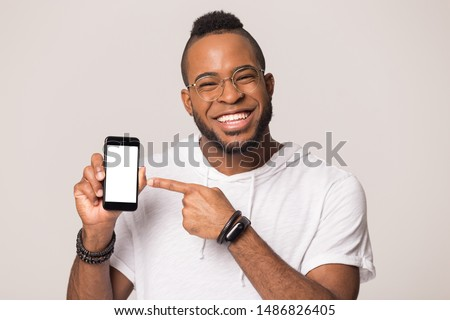 Smiling african American man stand isolated on grey studio background look at camera showing smartphone screen, happy black male in glasses hold cellphone point at good offer received on mobile
