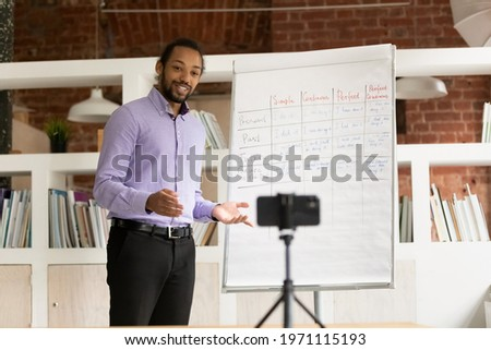 Smiling African American man teacher recording flip chart presentation, webinar on smartphone, mentor coach explaining, holding online lesson, using phone webcam, e-learning and distance education