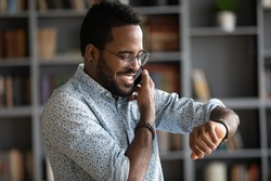 Smiling African American man wearing glasses checking time while making phone call close up, confident positive businessman planning meeting with partner, looking at wristwatch, task management