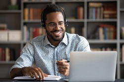 Smiling African American man wearing headphones looking at laptop screen, motivated student writing notes during online lesson, watching webinar, learning language online, sitting at work desk