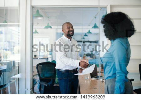 Smiling African American manager shaking hands with a new job applicant after an interview while standing together in his office  Stock photo ©