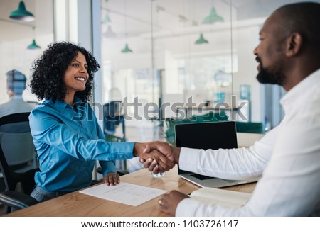 Smiling African American manager sitting at his desk in an office shaking hands with a potential new employee after an interview