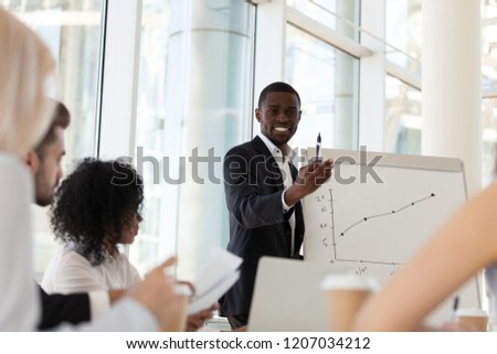 Smiling African American mentor or coach make presentation on flipchart, talking on strategies or plan, black businessman give training to office employees, explain graphics on whiteboard