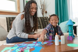 Smiling African American Mother and Child Learn About Science, Space and Rockets