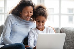 Smiling african american mother and kid daughter have fun shopping online at home, happy black mom teaching little mixed race child girl learn use laptop, watch cartoon, make video call on computer