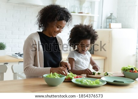Smiling African American mother with daughter cooking salad together, chopping fresh vegetables on board, sitting at wooden kitchen table, caring mum and child preparing meal, having fun