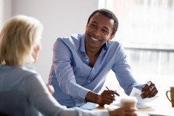 Smiling african american professional manager advisor designer talking with client listen to customer preferences at business meeting, diverse colleagues having conversation share design idea at work