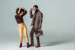 smiling african american retro styled couple dancing with vintage radio on grey