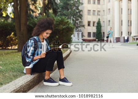 Smiling african-american student girl sitting on curb at college campus. Young woman reading notes outdoors, preparing for exams. Technology, education and entering the universityconcept, copy space