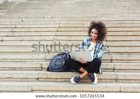 Smiling african-american student girl sitting on stairs working on laptop, preparing for exams outdoors, having rest in university campus. Technology, education and remote working concept, copy space Stock photo ©