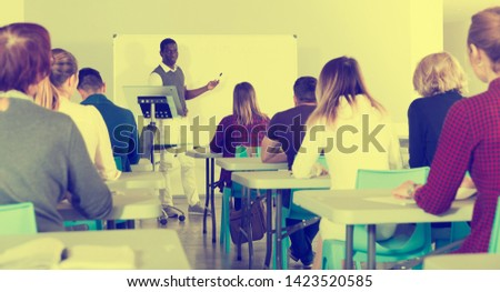 Smiling African American teacher giving presentation for students in lecture hall  #1423520585