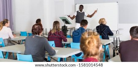 Smiling African American teacher giving presentation for students in lecture hall  #1581014548