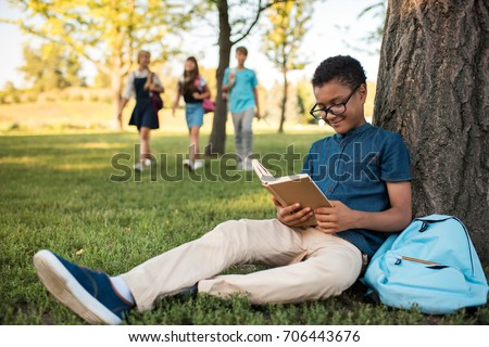 smiling african american teenage boy in eyeglasses studying in park
