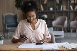Smiling African American woman in glasses calculating bills, using smartphone and calculator, positive young female browsing online banking service, analyzing financial documents, planning budget