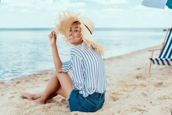 smiling african american woman in straw hat looking at camera while sitting on sandy beach with deck chair and beach umbrella