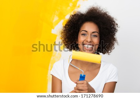 Smiling African American woman redecorating her house holding a paint roller covered in orange paint which she has been applying to the wall behind her