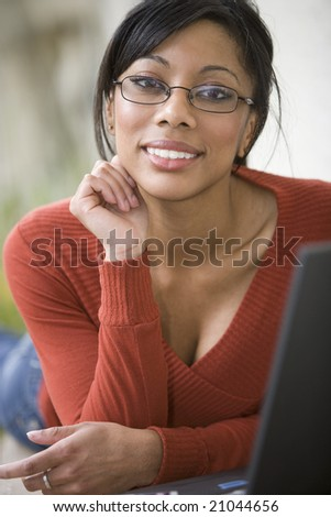 Smiling African American woman relaxing outside using her laptop