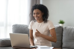 Smiling African American woman showing thumbs up, using laptop, making video call, satisfied student recommending distance education, teacher mentor recording webinar, working online at home