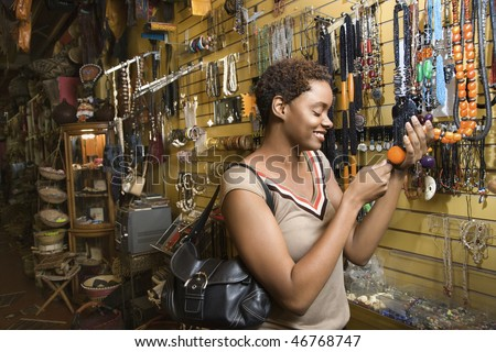 Smiling African American woman standing and looking at a retail display of necklaces. Horizontal format.