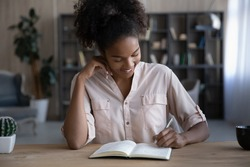 Smiling African American woman taking notes, writing in notebook, sitting at desk, confident businesswoman making schedule, planning workday, meetings, writing down ideas or important information