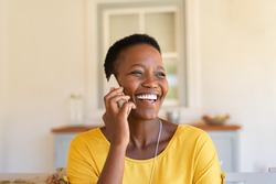 Smiling african american woman talking on the phone. Mature black woman in conversation using mobile phone while laughing. Young cheerful lady having fun during a funny conversation call.