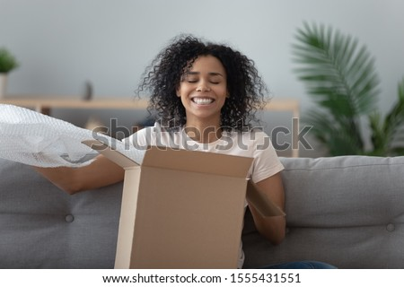 Smiling African American woman unboxing parcel, sitting on couch at home, excited girl removing bubble wrap, satisfied client received online store order, good delivery service concept