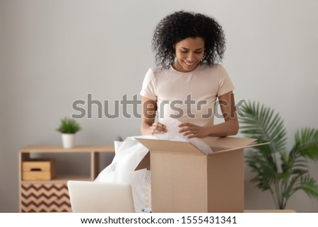 Smiling African American woman unpacking parcel, happy girl removing bubble wrap, looking in cardboard box, satisfied client received online store order, good delivery service concept