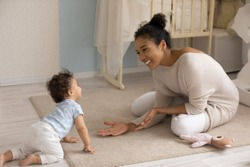Smiling african American young mom sit on floor in children room play with small biracial toddler baby. Happy loving ethnic mother have fun learn walking crawling at home. Childcare concept.